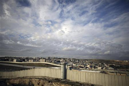 A section of Israel's controversial barrier runs in front of Qalandiya refugee camp near the West Bank city of Ramallah December 7, 2012. REUTERS/Ammar Awad