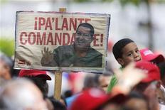 """Apoiadores do presidente venezuelano Hugo Chavez se reúnem para manifestar seu apoio e rezar por sua saúde na Praça Bolívar, em Caracas. Na placa se lê """"Siga adiante, comandante!"""" Chávez embarcou na madrugada desta segunda-feira para Cuba, onde será operado de emergência após sofrer uma recaída do câncer, que ele reconheceu que pode encerrar seu governo de 14 anos. 09/12/2012 REUTERS/Jorge Silva"""