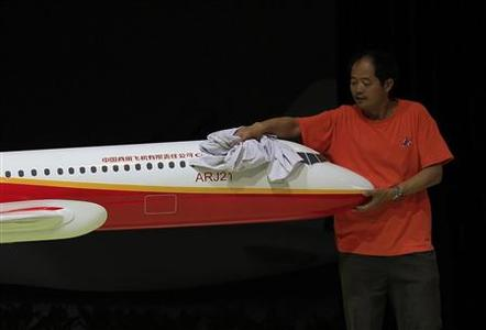 A worker cleans a model of a China-made ARJ21 passenger plane at the booth of the Commercial Aircraft Corporation of China (COMAC) as part of the China International Aviation & Aerospace Exhibition in the southern Chinese city of Zhuhai in this November 12, 2012 file photo. American International Group Inc (AIG) on December 9, 2012 said it would sell up to 90 percent of its ILFC airplane leasing business to a Chinese consortium led by New China Trust Co Ltd in a deal that values ILFC at $5.28 billion. Picture taken November 12, 2012. REUTERS/Bobby Yip/Files