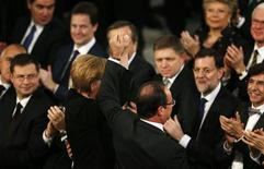 La Unión Europea (UE) recibió el lunes el Premio Nobel de la Paz, entregado por el comité noruego que reconoció sus décadas de estabilidad y democracia tras los horrores de dos guerras mundiales, pese a las actuales penurias europeas. En la imagen, la canciller alemana, Angela Merkel (centro I), y el presidente de Francia, François Hollande (centro D), levantan sus manos unidas durante la ceremonia del Premio Nobel de la Paz en el Ayuntamiento de Oslo, el 10 de diciembre de 2012. REUTERS/Suzanne Plunkett