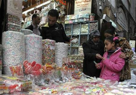 Girls buy candies at a shop in the old city of Damascus November 11, 2012. REUTERS/Muzaffar Salman