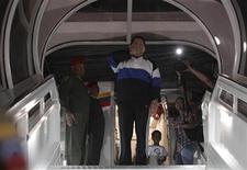 <p>El presidente de Venezuela, Hugo Chávez (al centro en la imagen), manda un beso desde la puerta de un avión antes de partir rumbo a Cuba desde Caracas, dic 10 2012. Chávez partió el lunes a Cuba para someterse a una nueva cirugía por el cáncer que lo persigue desde hace más de un año, y volvió a pedir a sus ministros que se mantengan unidos durante su ausencia. REUTERS/Miraflores Palace/Handout Imagen para uso no comercial, ni ventas, ni archivos. Solo para uso editorial. No para su venta en marketing o campañas publicitarias. Esta imagen fue entregada por un tercero y es distribuida, exactamente como fue recibida por Reuters, como un servicio para clientes.</p>