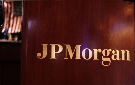 A flag hangs on the wall of the JP Morgan company stall on the floor of the New York Stock Exchange in New York July 15, 2010. REUTERS/Lucas Jackson