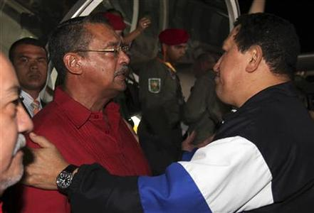 Venezuelan President Hugo Chavez embraces Vargas Governor Jorge Garcia Carneiro before departing to Cuba at Simon Bolivar airport in Caracas December 10, 2012. REUTERS/Miraflores Palace/Handout