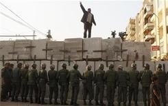 Manifestante anti-Mursi fala palavras de ordem diante de soldados que guardam entrada do palácio presidencial egípcio, no Cairo. O presidente islâmico do Egito, Mohamed Mursi, deu ao Exército poder temporário para prender civis e ajudar a proteger um referendo sobre a Constituição. 9/12/2012 REUTERS/Asmaa Waguih
