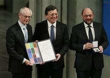 European Union (EU) representatives President of the European Council Herman Van Rompuy, President of the European Commission Jose Manuel Barroso and President of the European Parliament Martin Schulz (L-R) hold the Nobel Peace Prize certificate and medal after they accepted it on behalf of the EU during a ceremony at City Hall in Oslo December 10, 2012. REUTERS/Suzanne Plunkett