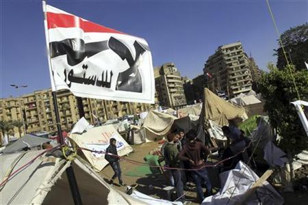 Anti-Mursi protesters sit outside their tents, below a flag that reads, ''No, to Constitution'' at Tahrir Square in Cairo December 10, 2012. The Egyptian government has given the military the authority to arrest civilians to help safeguard a constitutional referendum Islamist President Mohamed Mursi has planned for Saturday, the official gazette said. REUTERS/Mohamed Abd El Ghany (EGYPT - Tags: POLITICS CIVIL UNREST)