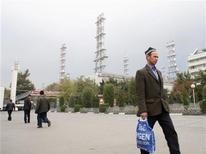 Рабочие идут мимо корпусов алюминиевого завода в Турсунзаде, Таджикистан 19 ноября 2012 года. Таджикистан стал вторым после Киргизии государством в Центральной Азии, получившим пропуск во Всемирную торговую организацию. REUTERS/Nozim Kalandarov