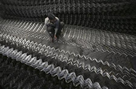 A labourer assembles iron chain link fence at a factory on the outskirts of Jammu March 1, 2012. REUTERS/Mukesh Gupta/Files