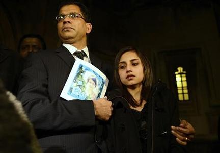 Lisha Barboza stands with her father Ben while he holds a picture of his wife, nurse Jacintha Saldanha, as they leave the Houses of Parliament in London December 10, 2012. REUTERS/Dylan Martinez