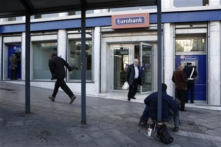 A beggar sits outside a Eurobank branch in Athens December 10, 2012. Greece received a total of 26.5 billion euros ($34.3 billion) in offers for its debt buyback at the close of business on December 7, a senior euro zone official told Reuters on Monday. REUTERS/Yorgos Karahalis
