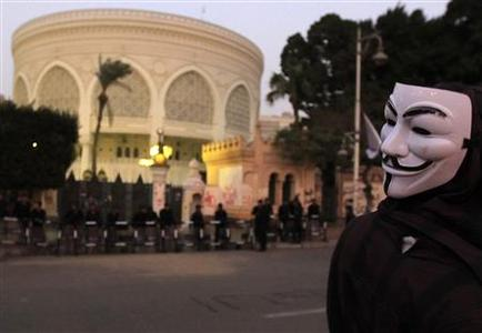 An Anti-Mursi protester, wearing a Guy Fawkes mask, stands in front of the presidential palace in Cairo December 10, 2012. REUTERS/Mohamed Abd El Ghany