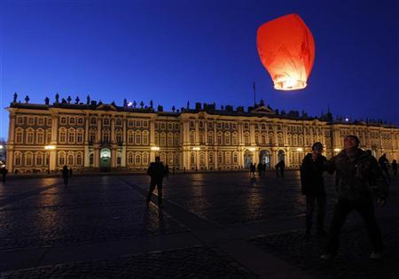 People launch floating paper lanterns into the sky in front of the Hermitage museum to mark Earth Hour in St. Petersburg March 31, 2012. REUTERS/Alexander Demianchuk