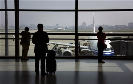 Passengers watch a China Southern Airlines plane take off as they wait to board their plane at Shanghai's Hongqiao International Airport in this April 16, 2012 file photo. In China, angry passengers are resorting to extreme measures to protest delays as the country's restricted air corridors are becoming clogged with millions of new fliers each year -- a fact attributed to the fast rise of the middle class and cheap flights. There have been dozens of incidents involving irate travellers on both domestic and international flights this year, as airlines struggle to stick to their schedules. REUTERS/David Gray/Files
