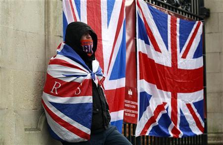 A Protestor draped in the Union Flag stands in front of Belfast's City Hall December 8, 2012. REUTERS/Cathal McNaughton