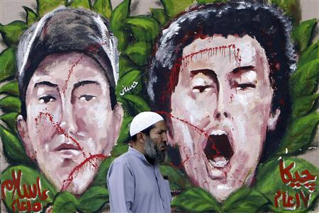 An anti-Mursi protester walks past graffiti depicting two activists who died recently, at Tahrir Square in Cairo December 10, 2012. REUTERS/Mohamed Abd El Ghany