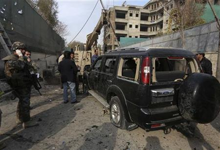 Afghan security personnel and NATO troops inspect the site of a suicide bomb attack in Kabul November 21, 2012. REUTERS/Omar Sobhani/Files