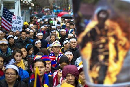 Protesters stand behind a photo of a victim of self-immolation during a solidarity march from the Chinese Consulate to the United Nations (UN) Headquarters in support of Tibet in New York December 10, 2012. REUTERS/Lucas Jackson