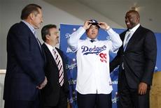 Los Angeles Dodgers' new left-handed pitcher Hyun-Jin Ryu of South Korea (2nd R) wears a cap as he puts on his new jersey while standing with general manager Ned Colletti (2nd L), owner Magic Johnson (R), and his agent Scott Boras at a news conference in Los Angeles, California, December 10, 2012. REUTERS/Lucy Nicholson