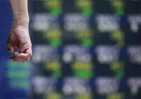 A man clicks his nails as he looks at an electronic board displaying share prices outside a brokerage in Tokyo September 20, 2012. REUTERS/Yuriko Nakao/Files