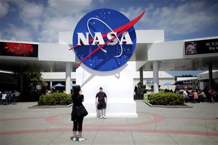 Tourists take pictures of a NASA sign at the Kennedy Space Center visitors complex in Cape Canaveral, Florida April 14, 2010. REUTERS/Carlos Barria/Files
