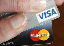A credit card user displays her cards in Washington February 22, 2010. REUTERS/Kevin Lamarque