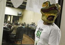 Costa Rica se convirtió el lunes en el primer país de América Latina en prohibir la caza como deporte, tras una votación unánime y final del Congreso. En la imagen, un ecologista lleva una máscara de una rana cerca de miembros del Congreso (detrás) mientras votan sobre la ley anti-caza, en San José, el 1 de octubre de 2012. REUTERS/Juan Carlos Ulate