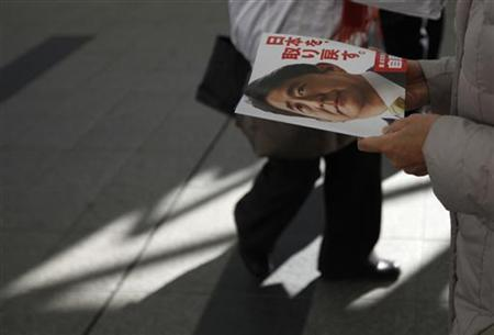 A woman holds an election campaign leaflet with a picture of Japan's main opposition Liberal Democratic Party's (LDP) leader and former Prime Minister Shinzo Abe during a campaign for December 16 lower house election in Ageo, north of Tokyo December 11, 2012. REUTERS/Shohei Miyano/Files
