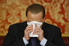 L'ex presidente del Consiglio Silvio Berlusconi si asciuga il viso durante una conferenza stampa. REUTERS/Alessandro Garofalo