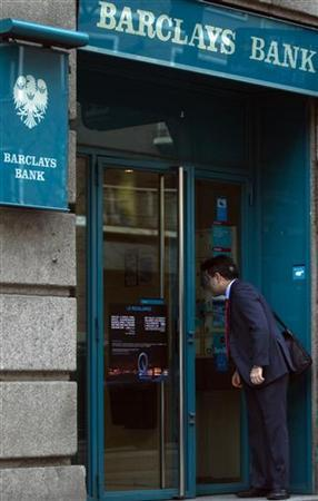 A man looks inside a Barclays bank branch in Madrid March 8, 2011. REUTERS/Sergio Perez