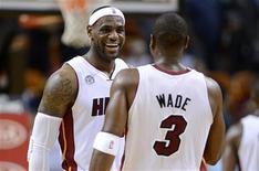 Los puntos de LeBron James y Dwyane Wade llevaron a los Heat de Miami a una victoria por 101-92 contra sus rivales de Atlanta, abriendo una brecha de 1,5 partidos respecto a los Hawks. En la imagen, LeBron James (I) y Dwyane Wade sonríen durante el partido contra Atlanta en Miami el 10 de diciembre de 2012. REUTERS/Rhona Wise