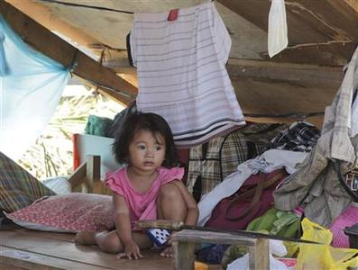 A girl rests inside a mekshift shelter in the coastal town of Cateel that was devastated during last Tuesday's Typhoon Bopha in Davao Oriental, southern Philippines December 11, 2012. Typhoon Bopha killed 647 people and caused crop damage worth 8.5 billion pesos ($210 million). the most intense storm to hit the Philippines this year wiped out about 90 percent of three coastal towns in Davao Oriental province and buried an entire town in neighboring Compostela Valley province under mud. REUTERS-Erik De Castro