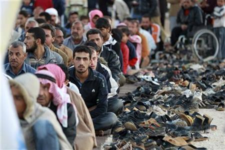 Syrian refugees wait to perform Eid al-Adha prayers at Al Zaatri refugee camp during the first day of Eid al-Adha in the Jordanian city of Mafraq, near the border with Syria, October 26, 2012. REUTERS/Muhammad Hamed
