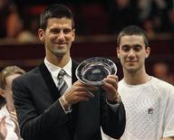 """Serbian tennis player Novak Djokovic with the """"Centrepoint Premier Award for Contribution to the Lives of Youth Across the World"""" in recognition of his Novak Djokovic Foundation at the Winter Whites Gala in aid of the homeless charity Centrepoint at the Royal Hall in London December 8, 2012. REUTERS/Luke MacGregor"""