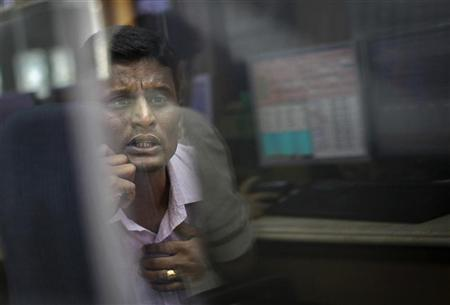 A broker looks at a computer screen as he talks on a phone at a stock brokerage firm in Mumbai December 3, 2012. REUTERS/Danish Siddiqui