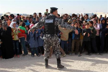 A Jordanian Gendarmerie officer gestures as Syrian refugees react during United Nations (U.N.) Secretary-General Ban Ki-moon's arrival to visit a U.N.-run school in Al Zaatri refugee camp, in the Jordanian city of Mafraq, near the border with Syria December 7, 2012. REUTERS/Muhammad Hamed (JORDAN - Tags: POLITICS SOCIETY CRIME LAW)