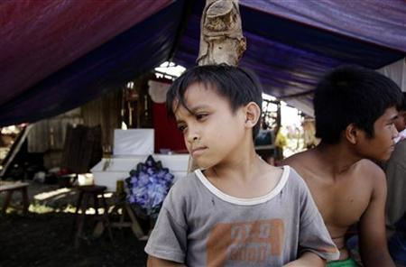 Typhoon victims sit at the entrance of a tent with a coffin of a relative, who died after a coconut tree fell on him at the height of Typhoon Bopha, in Montevista town, Compostela Valley in southern Philippines December 9, 2012. REUTERS/Erik De Castro