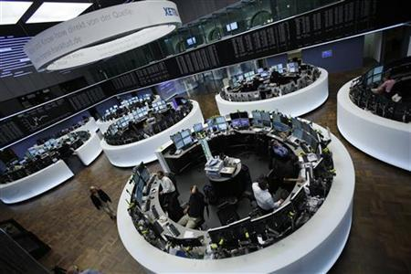 Traders work at their desks in front of the DAX board at the Frankfurt stock exchange September 12, 2012. REUTERS/Alex Domanski