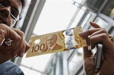 A man holds the new Canadian 100 dollar bill made of polymer in Toronto November 14, 2011. REUTERS/Mark Blinch