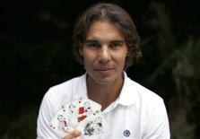 Spanish tennis player Rafa Nadal poses with playing cards depicting some of his 11 Grand Slam victories after an interview with Reuters in Madrid, September 18, 2012. REUTERS/Paul Hanna