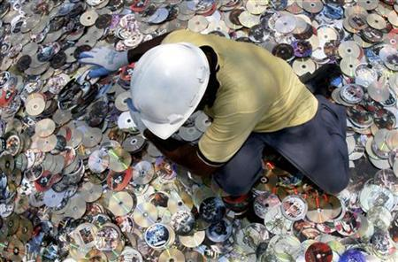 A worker sorts out a portion of about 35,000 confiscated pirated film DVDs as officials prepare to destroy them in Chennai March 23, 2007. REUTERS/Babu/Files