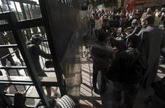 Manifestantes contrários ao presidente do Egito Mohamed Mursi tentam abrir portão que leva à rua em direção ao palácio presidencial. 11/12/2012 REUTERS/Amr Abdallah Dalsh
