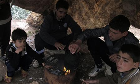 Syrian refugees warm themselves by a fire at a refugee camp in Atimeh, on the Syrian-Turkish border of the Idlib Governorate December 10, 2012. Picture taken December 10, 2012. REUTERS/Abdalghne Karoof
