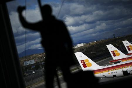 A man takes a photo of himself and Iberia airplanes parked on the tarmac at Madrid's Barajas airport November 29, 2012. REUTERS/Susana Vera