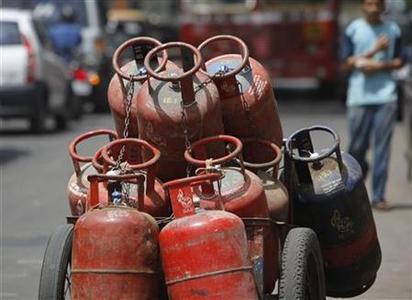 A man walks past gas cylinders loaded on a cart in Mumbai June 7, 2010. REUTERS/Danish Siddiqui/Files
