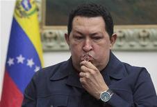 """El presidente venezolano Hugo Chávez """"está siendo operado en este instante"""" dijo el martes su homólogo ecuatoriano, Rafael Correa, quien en la víspera lo visitó en La Habana, donde está siendo tratado por la recurrencia de un cáncer. En la imagen, Chávez besa un crucifijo durante una emisión en directo en Caracas, el 8 de diciembre de 2012. REUTERS/Miraflores Palace/Handout"""