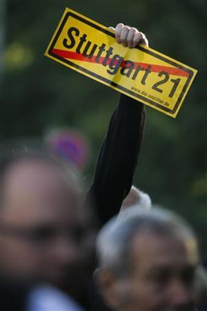 A demonstrator holds a placard during a protest against the Stuttgart 21 train station project, June 15, 2011. German rail operator Deutsche Bahn restarted work on the controversial Stuttgart 21 rail project on Tuesday. The project involves rebuilding the city's historical main station to make way for the Stuttgart 21 underground railway station. REUTERS/Alex Domanski (GERMANY - Tags: POLITICS TRANSPORT CIVIL UNREST)