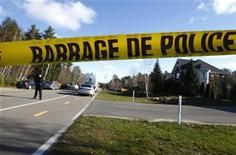 Police tape lines the road as Surete du Quebec officers investigate the street outside the home where the murder of reputed mafia member Joe Di Maulo took place in Blainville, Quebec, November 5, 2012. REUTERS/Christinne Muschi
