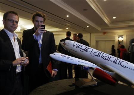 Attendees take pictures of aircraft models following a news conference announcing a sale of Virgin Atlantic airline to Delta Air Lines, in New York December 11, 2012. REUTERS/Brendan McDermid