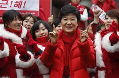 South Korea's ruling Saenuri Party's presidential candidate Park Geun-Hye (C) dances with election campaigners of the party during her campaign in Seoul December 7, 2012. Conservative and right wing Park is the daughter of late South Korean military dictator Park Chung-hee who took power in a military coup in 1961 and ruled until his assassination in 1979. If Park Geun-hye wins South Korea's presidential election on December 19 as now looks increasingly likely she will become the first woman to hold the country's top office, challenging stereotypes in a nation that is largely run by men in blue suits. Picture taken December 7, 2012. REUTERS/Lee Jae-Won